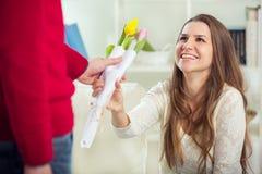 Молодой парень приносит цветки к его подруге Стоковое Изображение RF