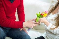 Молодой парень приносит цветки к его подруге Стоковая Фотография