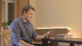 Молодой парень смотрит в новостях телефона акции видеоматериалы