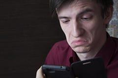 Молодой парень смотря в smartphone, унылую сторону Стоковая Фотография RF