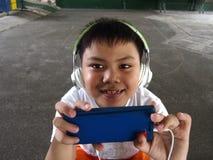 Молодой парень с smartphone и наушниками Стоковые Фото