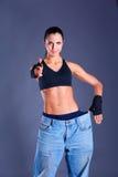 Молодой показ женщины фитнеса который ее старые джинсы и показывать о'кеы стоковое изображение rf
