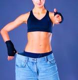 Молодой показ женщины фитнеса который ее старые джинсы и показывать о'кеы стоковые изображения rf