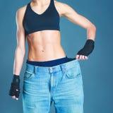 Молодой показ женщины фитнеса который ее старые джинсы стоковая фотография rf
