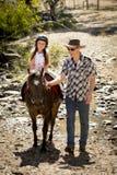 Молодой пони катания ребенк жокея outdoors счастливый с ролью отца как инструктор лошади в взгляде ковбоя Стоковое Фото