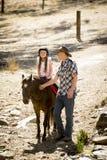 Молодой пони катания ребенк жокея outdoors счастливый с ролью отца как инструктор лошади в взгляде ковбоя Стоковые Изображения