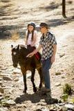 Молодой пони катания ребенк жокея outdoors счастливый с ролью отца как инструктор лошади в взгляде ковбоя Стоковые Фото