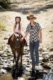 Молодой пони катания ребенк жокея outdoors счастливый с ролью отца как инструктор лошади в взгляде ковбоя Стоковое фото RF