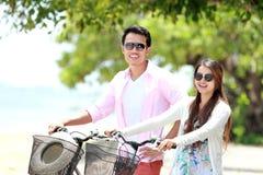 Молодой портрет пар с велосипедом на пляже стоковое фото rf