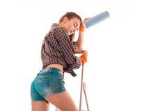 Молодой построитель женщины брюнет в форме делает реновации на лестнице и с роликом краски в изолированных руках на белизне Стоковое Изображение RF