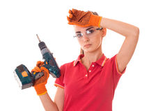 Молодой построитель женщины брюнет в форме делает реновации с просверлить внутри ее руки смотря и представляя на изолированной ка Стоковая Фотография