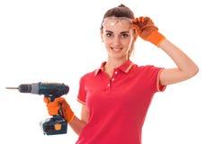 Молодой построитель женщины брюнет в форме делает реновации с просверлить внутри ее руки смотря и представляя на изолированной ка Стоковые Фотографии RF