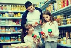 Молодой положительный усмехаться parents при залуживанное приобретение маленькой девочки Стоковые Фото
