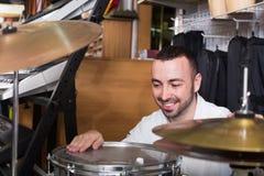 Молодой положительный человек покупая профессиональный комплект барабанчика Стоковые Фотографии RF