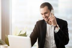 Молодой предприниматель отвечает звонку на рабочее место Стоковая Фотография