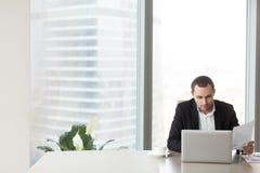 Молодой предприниматель сравнивает финансовые индикаторы стоковая фотография rf