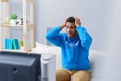 Молодой привлекательный африканский человек смотря телевидение Стоковые Фото