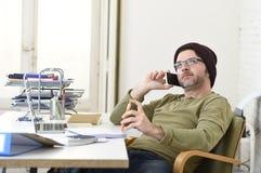 Молодой привлекательный бизнесмен битника работая от домашнего офиса с мобильным телефоном Стоковые Фото
