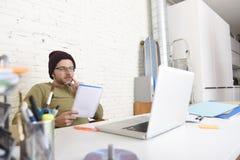 Молодой привлекательный бизнесмен битника работая с компьютером в современном домашнем офисе Стоковые Изображения