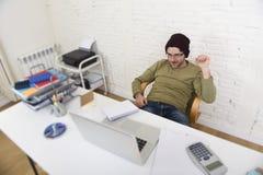Молодой привлекательный бизнесмен битника работая с компьютером в современном домашнем офисе Стоковое Фото