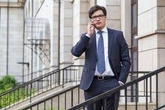 Молодой привлекательный бизнесмен на телефоне Стоковое Изображение RF