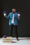 Молодой привлекательный бородатый человек битника, одетый в рубашке джинсовой ткани, стоит внутри помещения, держащ 2 белых бака  Стоковые Фотографии RF