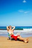 Молодой привлекательный вскользь бизнесмен ослабляя на пляже с Стоковые Изображения RF