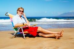Молодой привлекательный вскользь бизнесмен ослабляя на пляже Talkin стоковые изображения rf