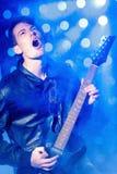 Молодой привлекательный музыкант утеса играя электрическую гитару и поя Рок-звезда на предпосылке фар Стоковые Изображения