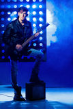 Молодой привлекательный музыкант утеса играя электрическую гитару и поя Рок-звезда на предпосылке фар Стоковое фото RF