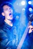 Молодой привлекательный музыкант утеса играя электрическую гитару и поя Рок-звезда на предпосылке фар Стоковые Изображения RF