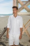Молодой привлекательный парень в белых одеждах представляя дальше Стоковое Фото