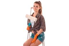 Молодой привлекательный построитель женщины брюнет в форме с роликом краски в ее изолированных руках делает reovations на белизне Стоковые Фото