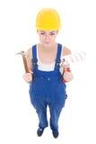 Молодой привлекательный построитель женщины в workwear с молотком и краской Стоковое Изображение