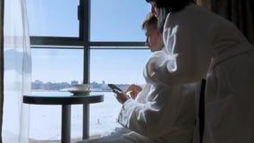 Молодой, привлекательный человек, бизнесмен сидя на таблице окном, выпивает чай, кофе и пишет текстовое сообщение сток-видео