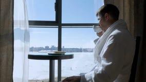 Молодой, привлекательный человек сидя на таблице чаем окна выпивая, кофе и писать сообщение SMS на черни видеоматериал