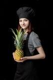 Молодой привлекательный шеф-повар женщины в черной форме держит свежий ананас на черной предпосылке Стоковая Фотография