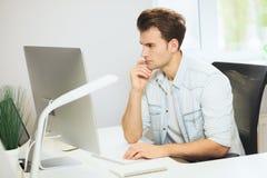 Молодой программист смотрит камеру График-дизайнер думает о будущих проектах Молодая ванта Стоковые Изображения RF