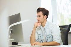 Молодой программист смотрит камеру График-дизайнер думает о будущих проектах Молодая ванта Стоковое Изображение