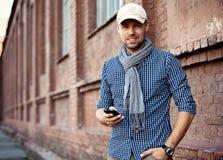 Молодой профессионал бизнесмена на smartphone идя в улицу используя сообщение sms app отправляя СМС на smartphone стоковое изображение