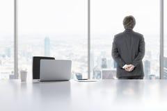 Молодой профессионал смотрит вне окно в современном панорамном офисе в Манхаттане, Нью-Йорке Компьтер-книжка, блокнот и a Стоковое Фото