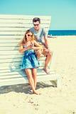 Молодой путешествовать пар, ослабляя на пляже в Нью-Джерси, США Стоковые Изображения