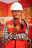Молодой плотник инженера нося квадратную рубашку flanel картины при красный жилет безопасности, держа зигзаг усмехаясь к камере Стоковое Изображение RF
