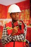 Молодой плотник инженера нося квадратную рубашку flanel картины при красный жилет безопасности, держа зигзаг усмехаясь к камере Стоковое фото RF