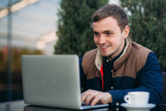 Молодой работник банка работает на компьтер-книжке на обеденном времени Стоковые Фото