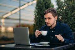 Молодой работник банка работает на компьтер-книжке на обеденном времени Стоковое Фото