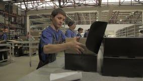 Молодой работник в форме кладет большую современную лампу приведенную в коробку акции видеоматериалы