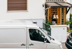 Молодой работник доставляющий покупки на дом держа коробку пакета картона звеня на d Стоковые Изображения