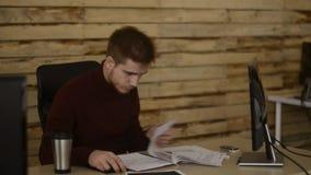 Молодой работник офиса cheking его документы перед компьютером на офисе Закручивать лихтер курильщица сток-видео