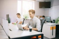 Молодой работник сидя в офисе на компьютере Фрилансер в белой рубашке Дизайнер сидит перед окном внутри стоковые изображения rf